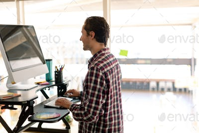 Side view of Caucasian male graphic designer working on computer at desk in office