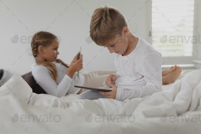 Side view of Caucasian siblings using digital tablet on bed in bedroom at comfortable home