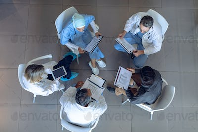 High angle view of diverse medical team discussing documents with each other in hospital