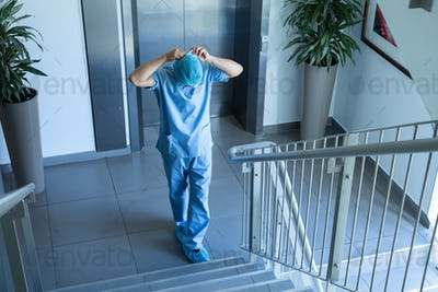 High angle view of Caucasian male surgeon wearing surgical mask while standing at stairs