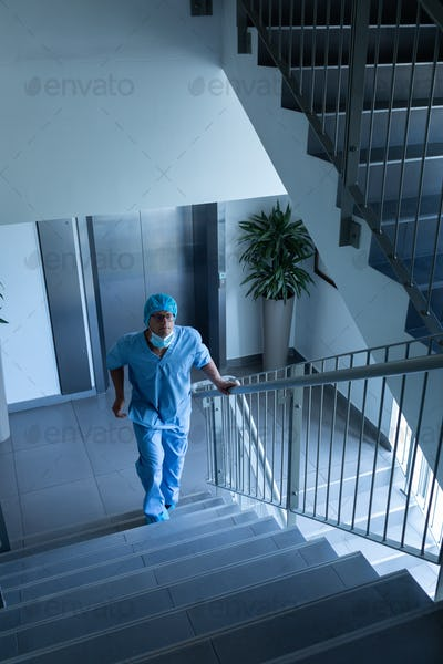 High angle view of Caucasian male surgeon walking upstairs in hospital