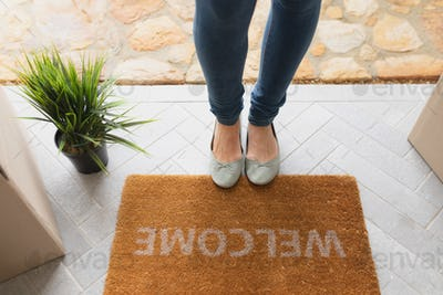 Low section of Caucasian woman standing near welcome mat in front of door at home