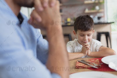 Caucasian father and son praying before having lunch at dining table