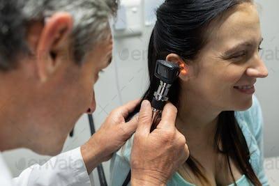 Caucasian male doctor examining a pregnant Caucasian woman