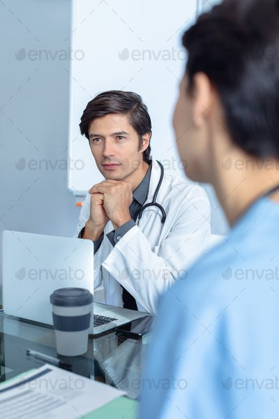 Male Caucasian doctor attentive to female Caucasian woman sitting and discussing at the table