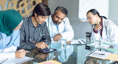 Diverse medical team with stethoscopes around the neck discussing x-ray report on digital tablet