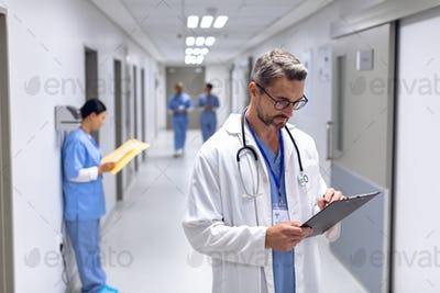 Caucasian male doctor writing on clipboard in corridor at hospital.