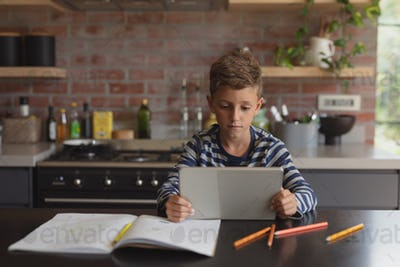 Front view of adorable Caucasian boy using digital tablet at table in kitchen at home