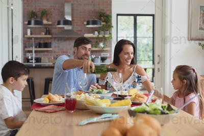 Front view of happy Caucasian family having food and champagne on dining table at home