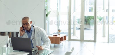 Mixed-race male doctor talking on mobile phone while using laptop at table