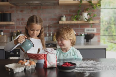 Front view of Caucasian siblings preparing cookie dough on worktop in kitchen in a comfortable home