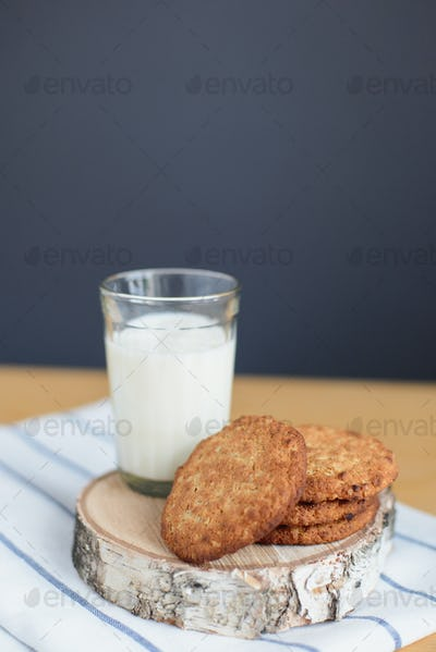 round brown wholegrain flour cookies and milk glass on striped white napkin on wooden table