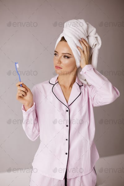 Cute lady in sleepwear standing with towel on her head toothbrush in hand dreamily looking aside