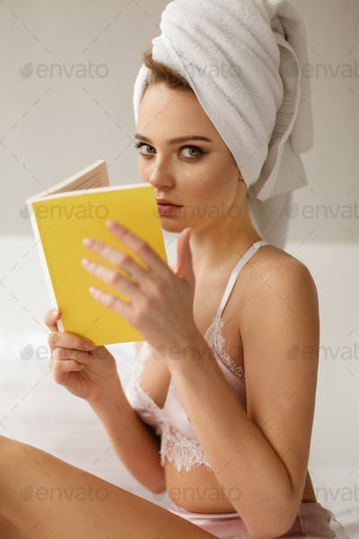 Pretty lady sitting in bed with towel on her head thoughtfully looking in camera with book in hands