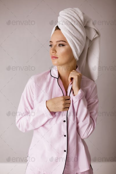 Beautiful lady in pink sleepwear standing with towel on her head and dreamily looking aside