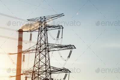 power transmission tower and chimney at dusk