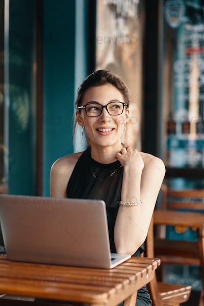 Refined business woman in glasses, sitting at table in cafe working at laptop