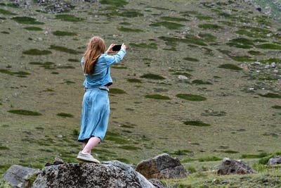 Back view female hiker takes photo of beautiful mountains in North Caucasus