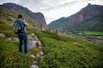 Male hiker takes photo of beautiful mountains and ancient tombs. North Caucasus