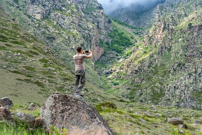 Male hiker takes photo of beautiful mountains in North Caucasus in summer