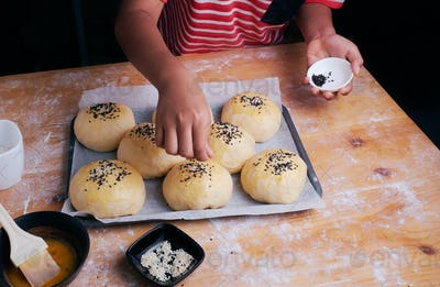 Sprinkle the sesame seeds on the dough of buns