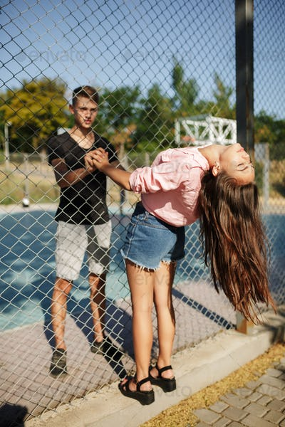 Young beautiful couple standing between mesh fence and holding hands other on basketball court