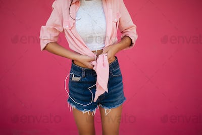 Photo of slim girl body standing in denim shorts and shirt on pink background