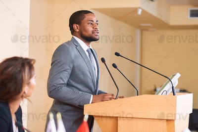 Young African-american male speaker talking in microphone