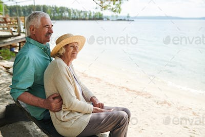 Senior romantic man and woman sitting on the beach