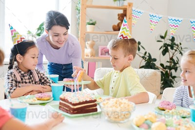 Smiling mom offering fresh homemade donuts to group of little friends