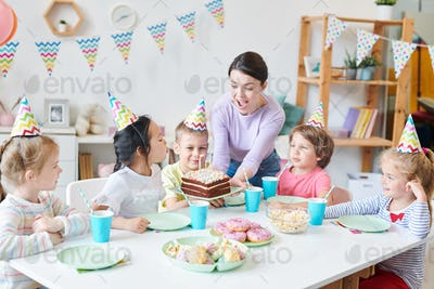 Ecstatic young woman holding birthday cake and looking at candles