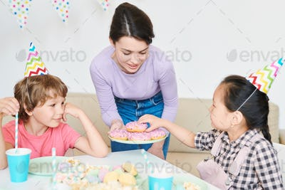 Little girl in birthday cap taking donut from plate held by mother