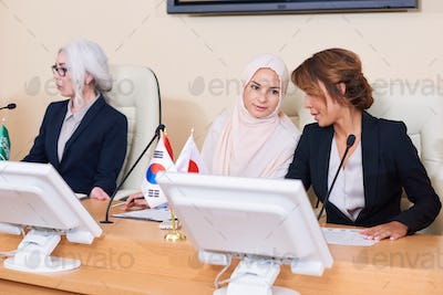 Two young elegant intercultural females consulting about report