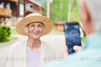 Happy senior female in elegant straw hat