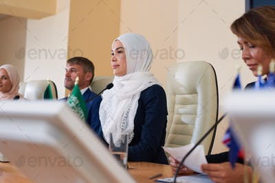 Young female muslim speaker and her foreign colleagues