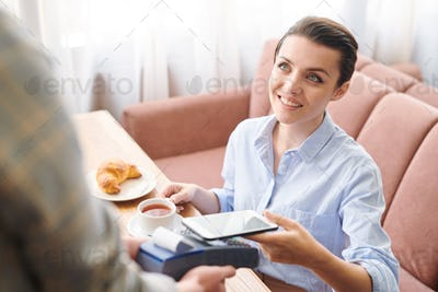 Pretty lady paying for breakfast