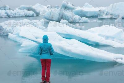 Tourist admiring floating icebergs in Jokulsarlon, Iceland