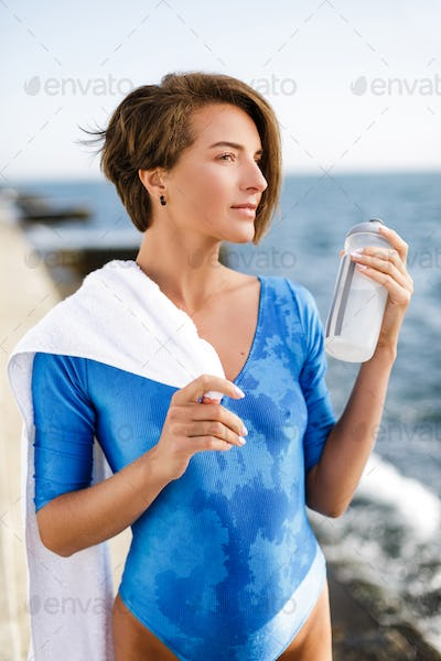 Woman in swimsuit with white towel on shoulder and bottle in hand while thoughtfully looking aside