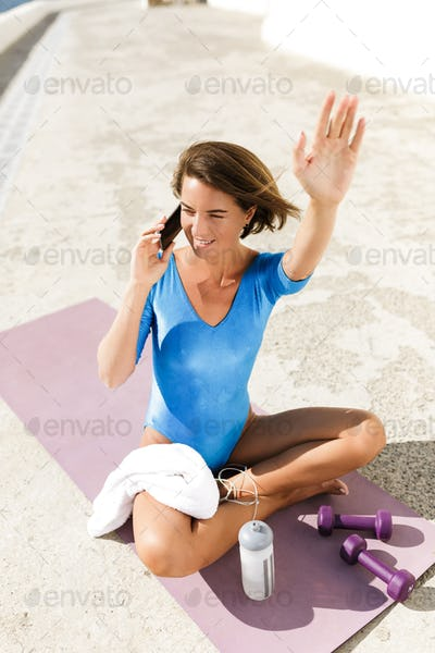 Cute woman in blue swimsuit sitting on yoga mat and talking on cellphone while happily waving hand