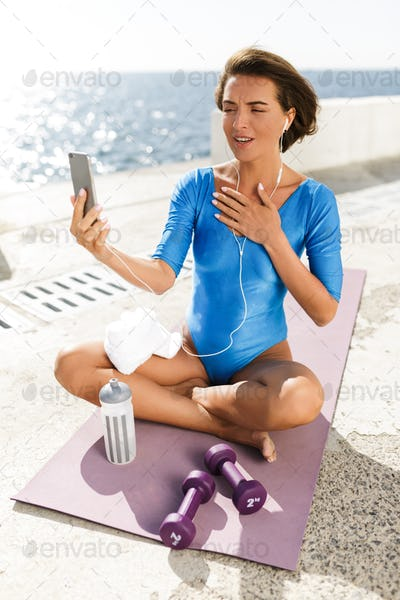 Beautiful woman in swimsuit on yoga mat thoughtfully looking in cellphone and talking by video call