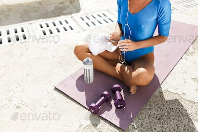 Photo of woman body in blue swimsuit sitting on yoga mat in lotus pose with cellphone in hands