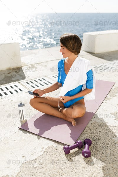 Smiling woman in blue swimsuit sitting on yoga mat using her cellphone with sea view on background