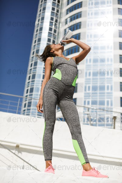 Beautiful woman in modern gray sport suit and pink sneakers drinking water with skuscrapers view
