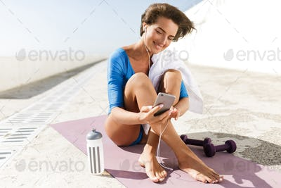 Cheerful woman in blue swimsuit and earphones sitting on yoga mat and happily looking in cellphone