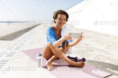 Happy woman in blue swimsuit and earphones sitting on purple yoga mat and using cellphone
