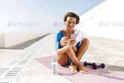 Cute smiling woman in blue swimsuit and earphones sitting on purple yoga mat and using cellphone