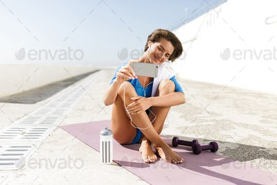 Beautiful smiling woman in blue swimsuit and earphones sitting on purple yoga mat taking selfie