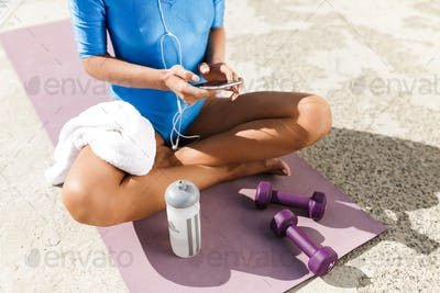 Female body in blue swimsuit sitting on purple yoga mat in lotus pose and holding cellphone in hands