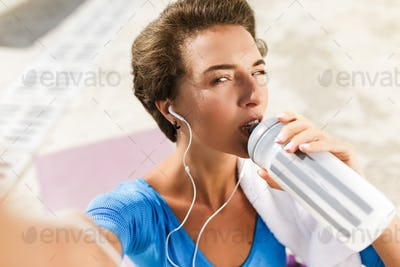 Woman in swimsuit sitting on yoga mat drinking water and taking selfie
