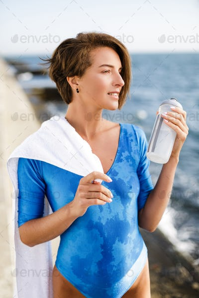 Beautiful woman in blue swimsuit with towel on shoulder and bottle in hand dreamily looking aside